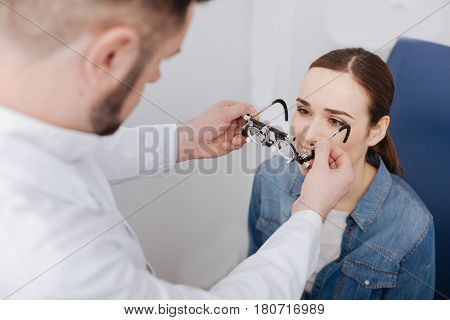 For eyesight diagnostics. Nice serious professional doctor standing in front of his patient and putting eye examination glasses on her while testing her eyesight