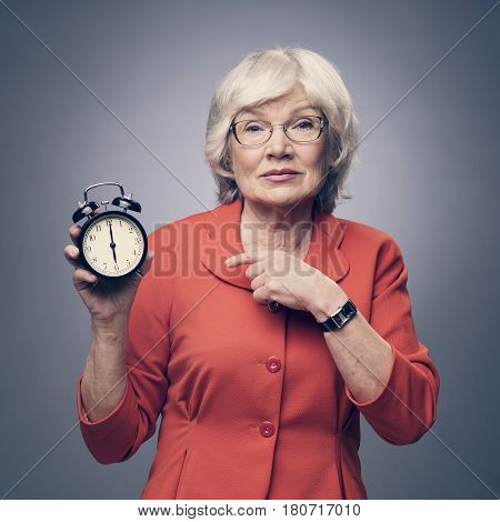 Senior Lady Pointing To Alarm Clock