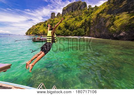 Young man jumping into the sea at koh chicken islands andaman sea Krabi South of Thailand