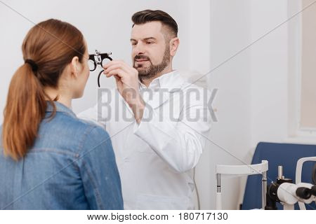 Eye testing glasses. Serious pleasant male oculist standing in front of his patient and putting eye testing glasses on her while doing a vision examination