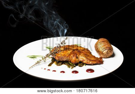 Fried turkey steak with potatoe and smoked rosemary and red sauce.
