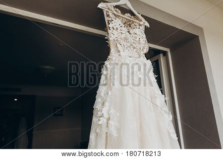 Luxury Wedding Dress With Flowers Hanging On Window In A Hotel Room. Modern Amazing Bride's Gown In