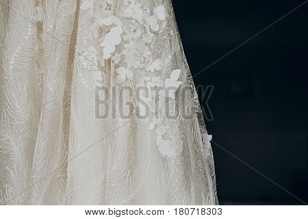 Luxury Wedding Dress Detail, Hanging On Window In A Hotel Room. Modern Amazing Bride's Gown With Flo