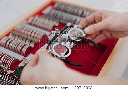 Being careful. Close up of eye examination glasses being carefully taken out of the box by a professional experienced optician