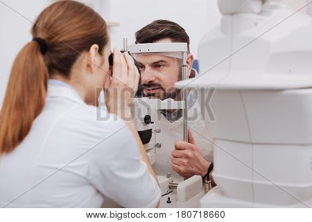 Eyesight problems. Pleasant professional female doctor looking into the special medical device and testing the vision of her patient while detecting eyesight problems