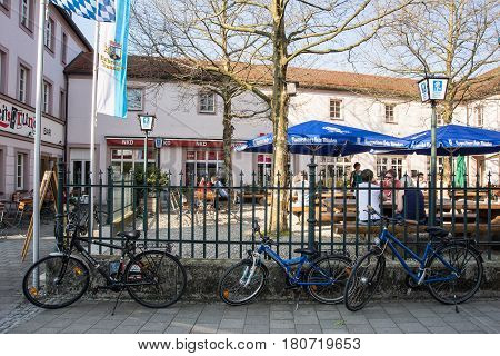Altoetting,Germany-April 9,2017:Bicycles stand in front of a beergarden while its owners sit in the terrace