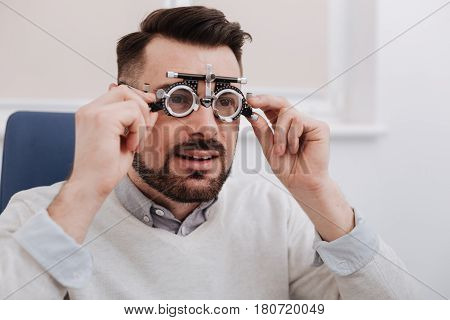 Eyesight test. Nice handsome bearded man sitting in the chair wearing eye testing glasses while visiting an ophthalmologist