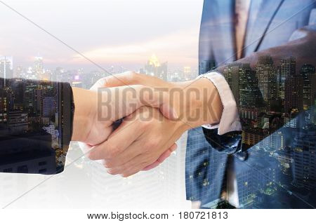 Double exposure of businessman and businesswoman handshake agree deal with city of business in blue tone background