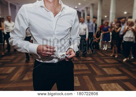 Groom Holding Silk Garter Lingerie From Bride Leg And Preparing To Throw It To Men At Wedding Recept