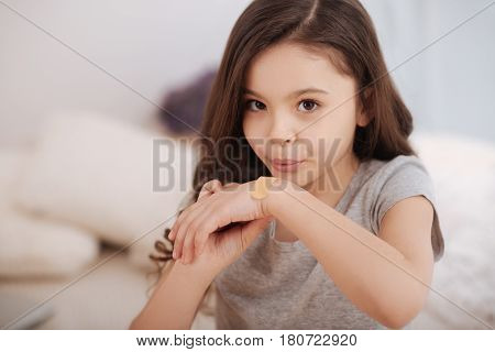 Full of confidence. Skilled cute little girl sitting in the bedroom and applying adhesive bandage on the hand while blowing on it