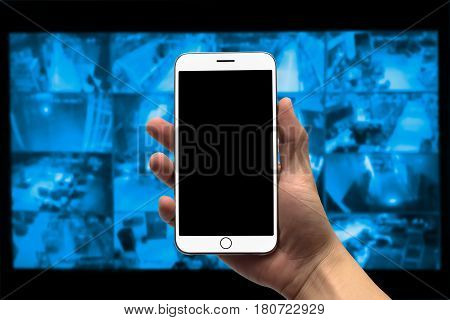 blurred photo Blurry image closed circuit camera security system with blank screen cell phone in hand.