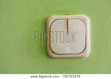 Two keys beige light switch mounted on green wall