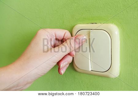 Female hand pressing two keys beige light switch mounted on green wall