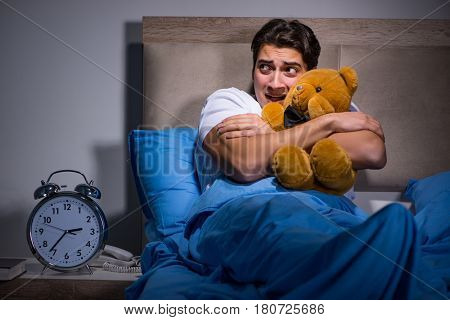 Young man scared in bed