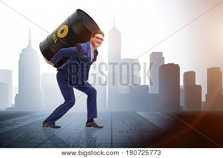 Businessman under the burden of oil barrel