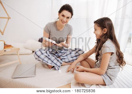 Taking care of bruise . Smiling skilled young woman sitting at home and using ointment while taking care of her daughter and enjoying weekend
