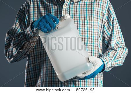 Unrecognizable male farmer with unlabeled plastic tank canister containing pesticides for plant processing in agriculture
