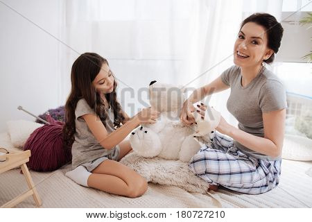 Enjoying our sunny morning. Skillful positive young mother sitting in the bedroom and holding adhesive bandage while her little child hugging fluffy bear and expressing delight