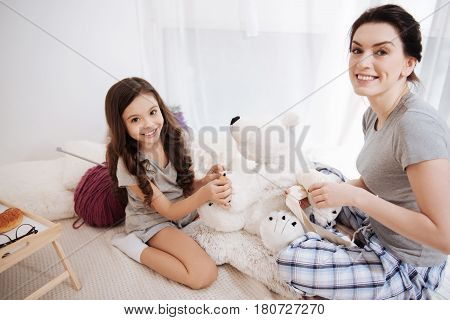 Enjoying doctors responsibilities. Cheerful caring young mother sitting in the bedroom and holding adhesive bandage while her little kid hugging fluffy bear and enjoying medicine procedures