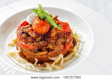 Mexican food - beef fajitas with peppers and pasta on white plate close up.