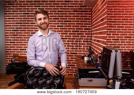 Barber expert smiling and looking at camera and keeping hand on chair while standing at barbershop against brick wall. Portrait of hairdresser in the shirt. Horizontal photo. Mirror and barber tools. Professionalism and craftsmanship.