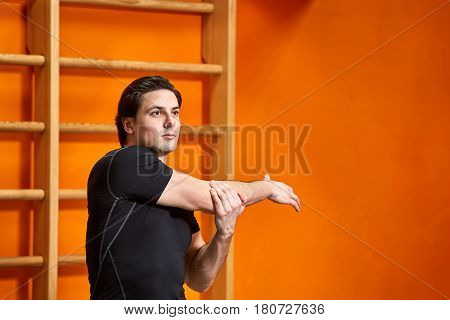 Sportsman in the black sportwear at the gym doing stretching exercises against bright orange wall. Stretching arms. Portrait of the beautiful athletic man. Horizontal photo. Healthy lifestyle.