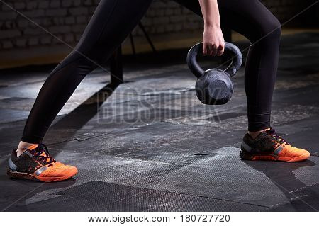 Closeup photo of young woman's legs in leggings and sneackers and kettlebell against dark background. Crossfit workout. Detail of crossfit woman. Healthy lifestyle.