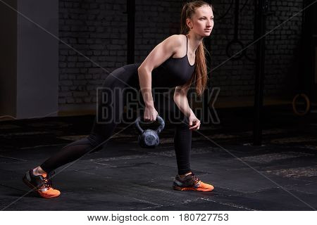 Sporty young woman with muscular body doing crossfit workout with kettlebell on dark background. Sporty woman in the black sportwear, t-shirt, leggings and orange sneackers. Concept of crossfit activity.