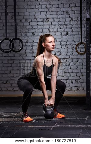 Sporty young woman with muscular body doing crossfit workout with kettlebell against brick wall. Sporty woman in the black sportwear, t-shirt, leggings and orange sneackers. Concept of crossfit activity.