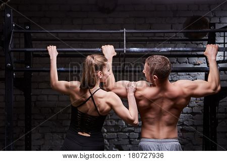 Rear photo of young attractive caucasian crossfit man and woman while working out in gym. Young couple. Exercising on chin-up bar, doing pull-ups for arms and back muscles. Background with brick wall. Healthy lifestyle.