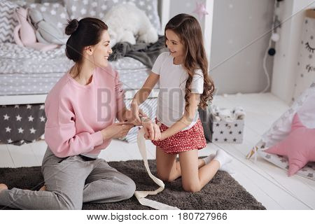 Enjoying medicine lesson with my mother. Lively little gifted girl sitting in the night nursery and caring about mother while using elastic roller and bandaging
