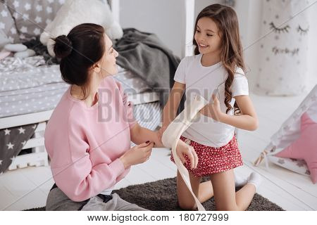 Spending funny weekend together. Happy little gifted kid sitting in the night nursery and caring about mother while using elastic roller and bandaging