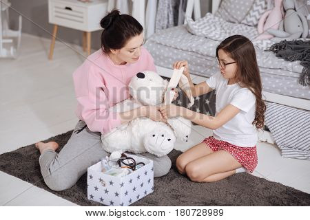 Upbringing my child. Smiling helpful caring mother sitting in the night nursery and holding plush toy while her little daughter treating it and bandaging