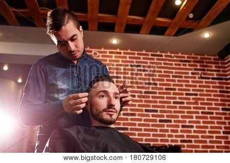Close up side view of young bearded man getting groomed by hairdresser with comb against brick wall at barbershop. Two man, master and client. Interior of the barbershop. Professionalism and craftsmanship.