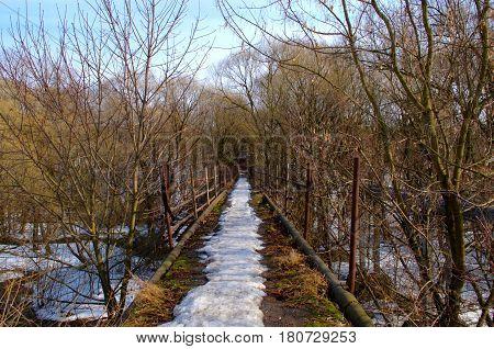 Old pedestrian bridge across a small river