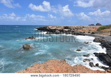 Aqua tropical waters off of Aruba's east coast and the black sand stone beach.