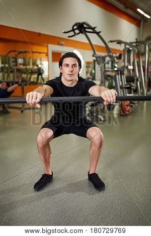 Young athletic man in black sportwear with bar of barbell flexing muscles in gym. Sportsman in the t-shirt, shorts and sneackers. Power and energy. Exercises and squatting. Concept of the healthy lifestyle.