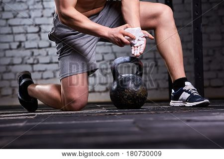 Close-up photo of young athlete man getting ready for crossfit training against brick wall. Sportsman in the sporty shorts and sneackers. On the floor is kettlebell. Horizontal photo. Healthy lifestyle.