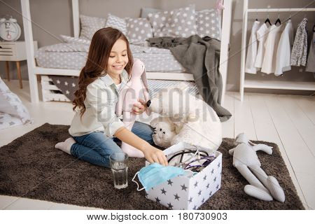 Enjoying playing games. Smiling optimistic positive girl sitting in the night nursery while having fun and playing with toys
