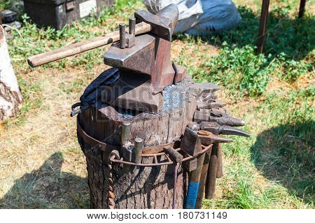 Old anvil with blacksmith tools at the outdoors