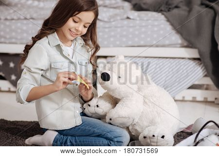 Full of positivity. Happy glad charming child sitting in the night nursery and enjoying being doctor while treating fluffy bear