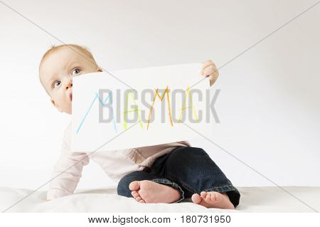 Funny infant kid looking out for poster with sign Mama. Awesome toddler boy holding big postcard for Mothers day.