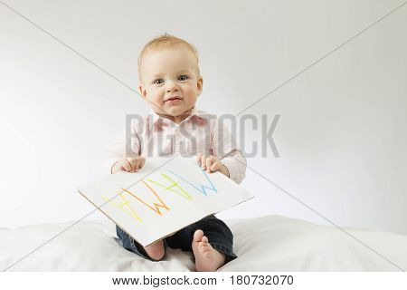 Smiling baby looking at camera. Cute infant kid holding sign Mama on big postcard.