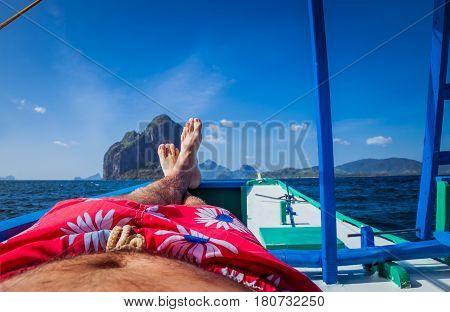Man laying in banca boat, feet facing Inabuyatan Island by El-Nido, Palawan, Philippines.