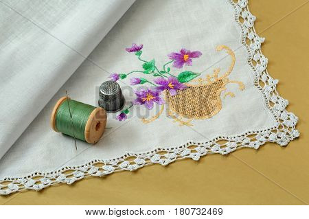 Thread with a needle a thimble and a handkerchief