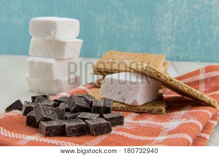 Deconstructed Smore on Orange Napkin with stack of marshmallows behind