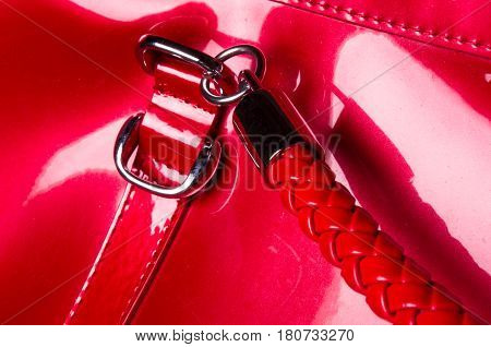 closeup of buckles, clasps, zippers, pockets, fasteners, fittings and seams on the red lacquer hand bag