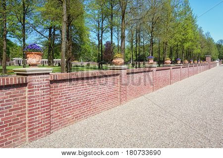 Stone wall decorated with violets filled earthenware pots in the Dutch baroque garden of The Loo Palace.