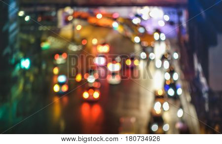 Multicolored bokeh of cars at rush hour in Bangkok city urban area - Defocused traffic jam in highway intersection - Transport concept with blurred vehicles at night - Dark vivid color tones filter