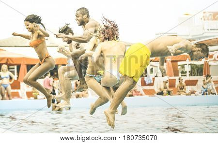 Side view of multiracial friends jumping at swimming pool party - Vacation concept with happy guys and girls having fun in summer day at leisure aquapark - Active young people on retro contrast filter
